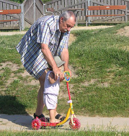 Grandpa teaching grandson scooter